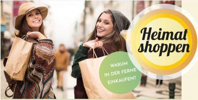 Zwei jüngere Frauen mit Einkaufstüten shoppen vor Ort